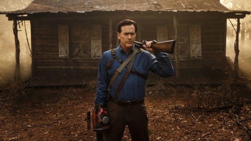 Ash con su motosierra y su escopeta (boomstick) con la vieja cabaña de fondo, los 80 nunca mueren.